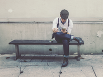 Man Sitting on Bench looking at smartphone