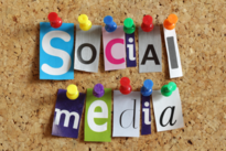 Social Media spelled out in magazine cut-outs stuck to a cork board with thumbtacks