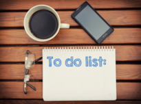 To Do List written on notepad next to a pair of glasses, coffee cup and cell phone on a table.