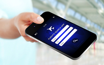Hand holding mobile phone with flight search app open