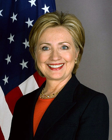 Headshot of Hillary Clinton in front of the US flag
