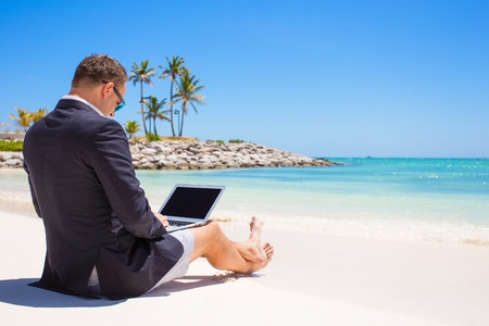 Picture of man in suit jacket and shorts sitting on beach with laptop on lap.